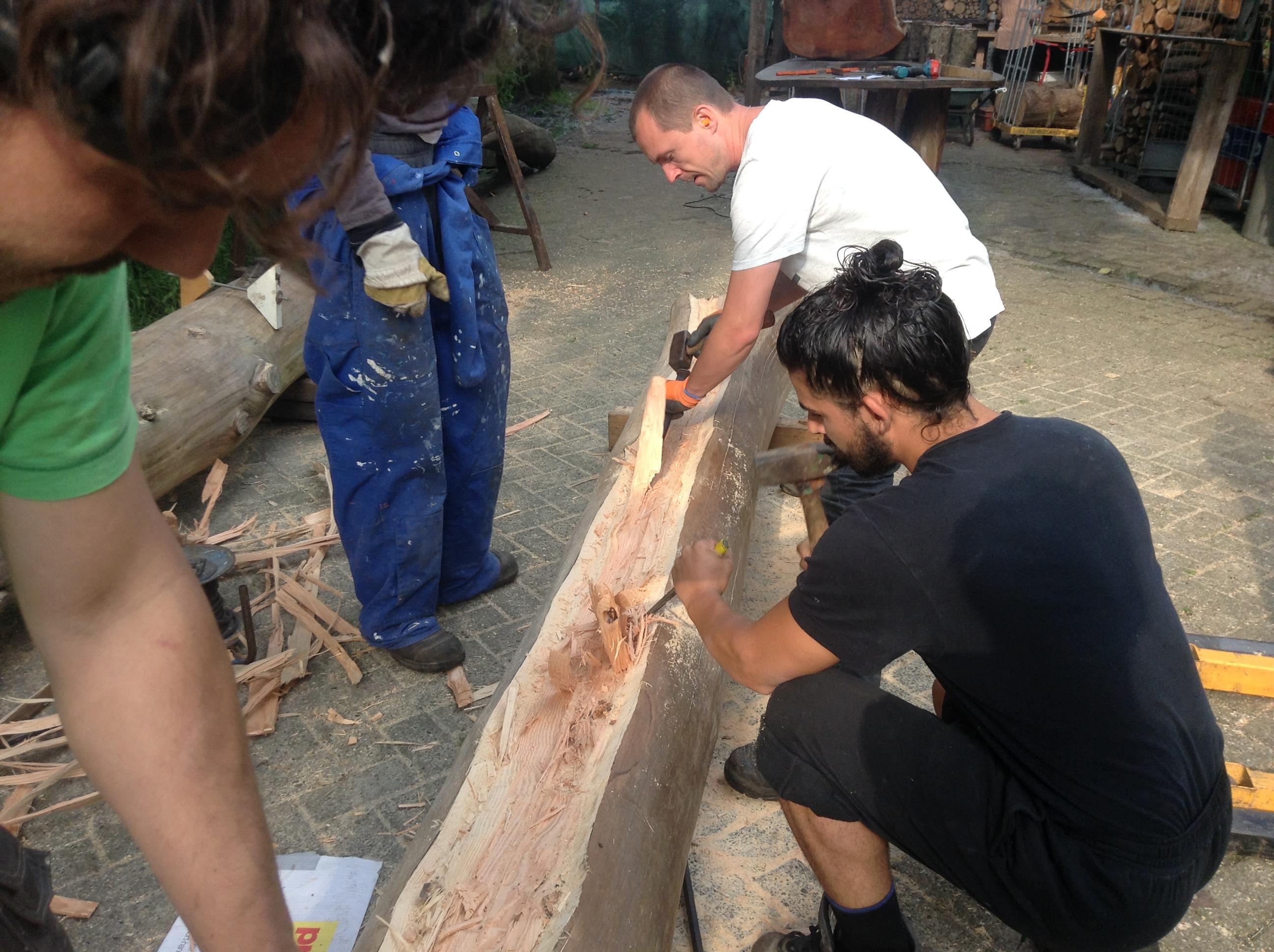 Met grote houtbeitels wordt het hout bewerkt